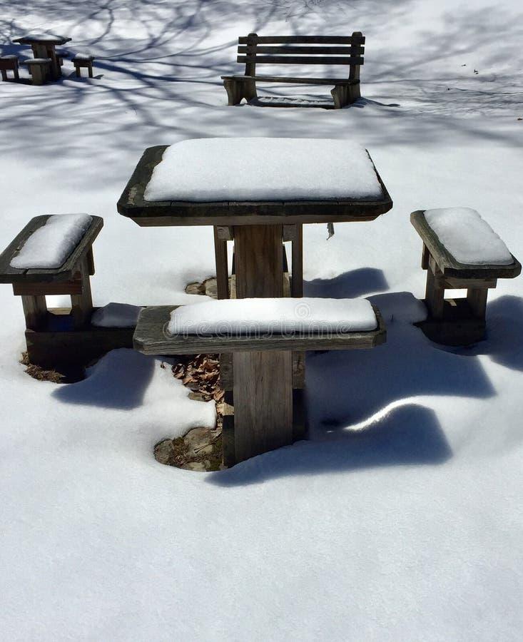 Sneeuw en schaduwen op de lijst van de cementpicknick stock afbeeldingen