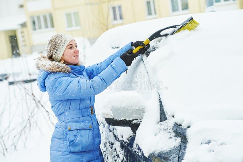 Sneeuw het schoonmaken Vrouwen schoonmakende auto van sneeuw in de winter stock fotografie