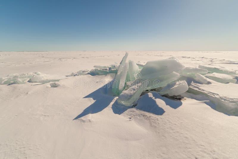 Sneeuw, ijs, heuveltjes op snow-covered ijs van meer. Een natuurlijke winte stock fotografie