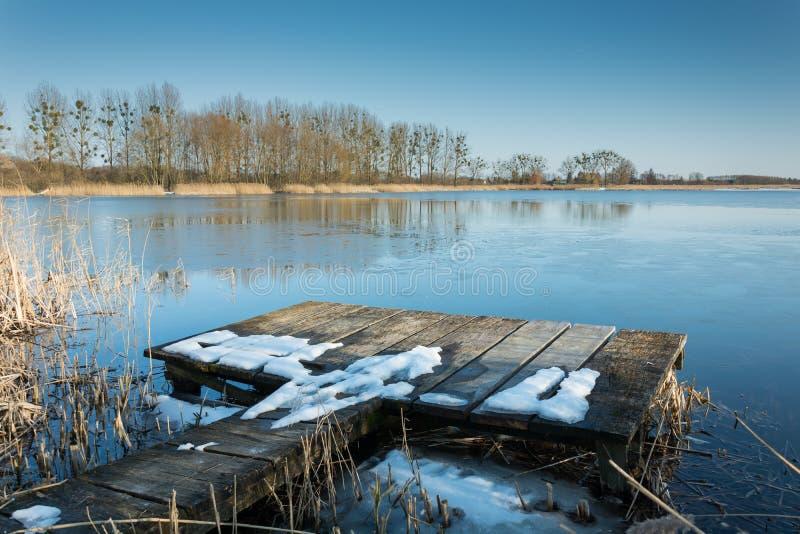 Sneeuw op een houten visserijpijler op het meer Bomen op de kust die in het water nadenken stock afbeeldingen