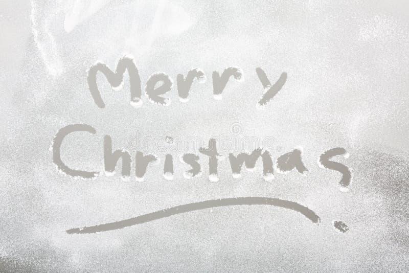 Sneeuw op het bevroren venster met woord Vrolijke Kerstmis stock afbeeldingen
