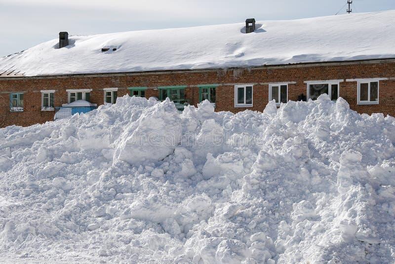 Sneeuwbank voor een baksteenhuis royalty-vrije stock afbeeldingen