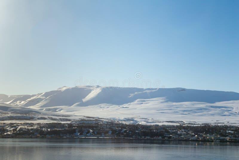 Sneeuwberg over klein dorp met duidelijke blauwe hemel stock foto's