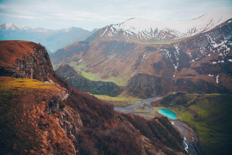 Sneeuwbergen en blauw meer in groene vallei stock fotografie