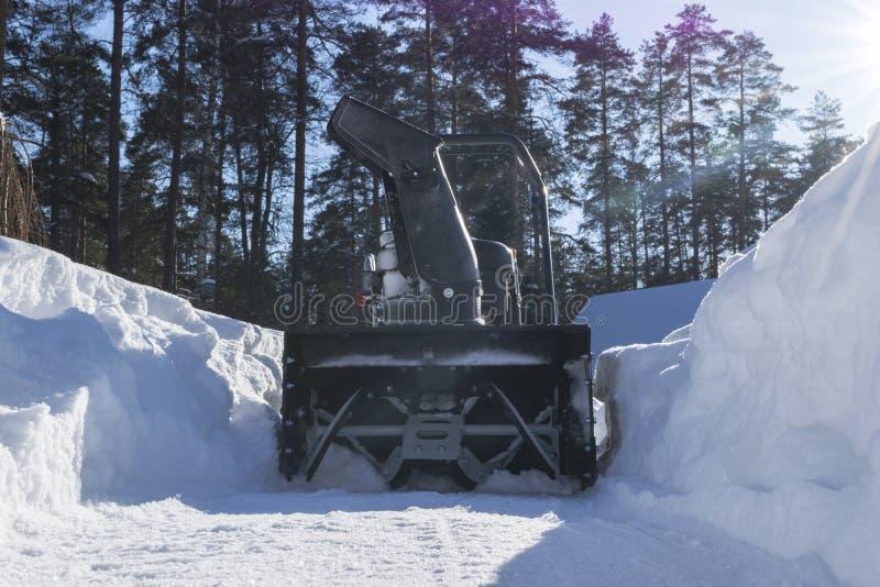 Sneeuwblazer op het werk op een de winterdag Sneeuwploeg die sneeuw na blizzard verwijderen Het ontruimen van het ijs De machine  stock afbeelding
