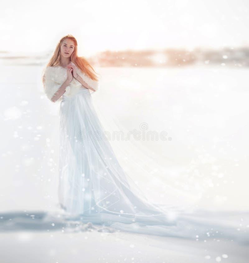 Sneeuwfee, de sneeuwkoningin Meisje in een witte kleding die zich in de sneeuw, prachtige manier bevinden Kerstmisfee stock foto's