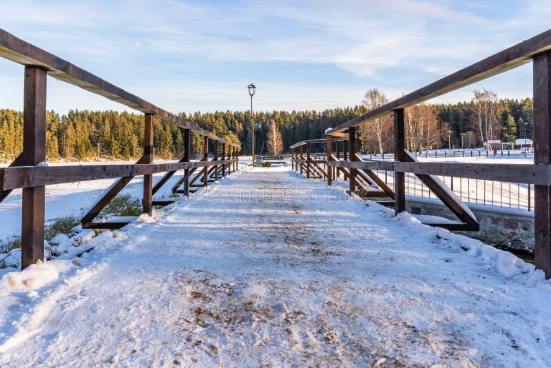 Sneeuwfoto van het Park op een Sunny Winter-dag - Houten Voetpad in het midden van het, Concept de Harmonie en Reis royalty-vrije stock afbeelding