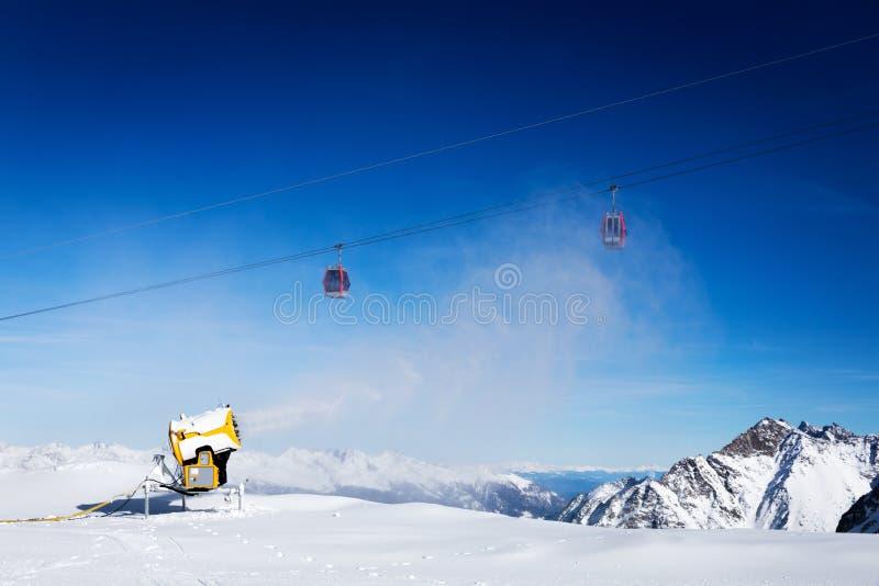 Sneeuwkanon die tegen blauwe zonnige hemel bij skitoevlucht werken stock fotografie
