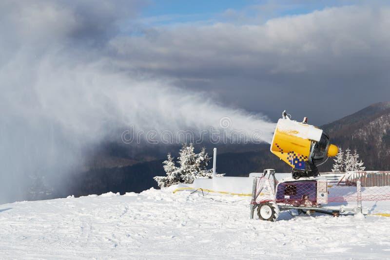 Sneeuwkanonmachine aan het werk op een skipiste, in het skidomein Azuga, in de regio Prahova Valley, Roemenië stock foto