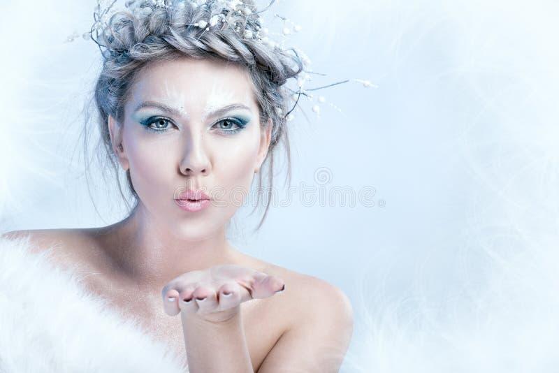 Sneeuwkoningin die in haar hand blazen stock afbeeldingen