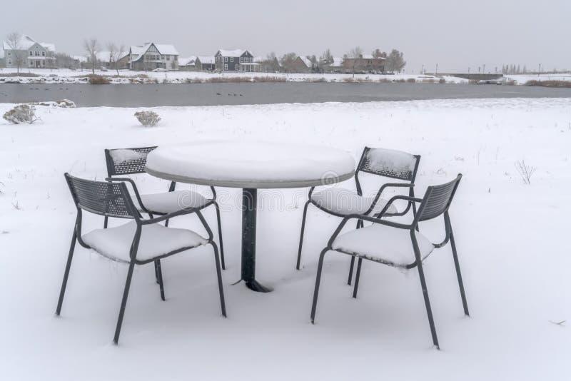 Sneeuwlijst en stoelen op een lakeshore in Dageraad royalty-vrije stock foto's
