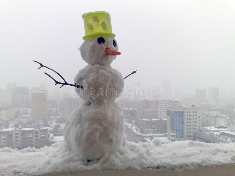 Sneeuwman in de stad stock foto