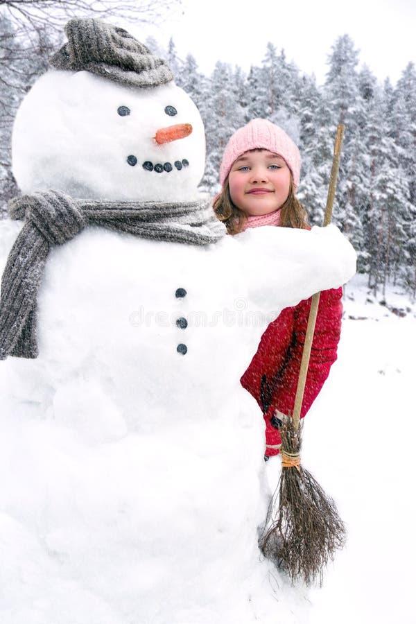Sneeuwman en een jong meisje buiten in sneeuwval stock foto's