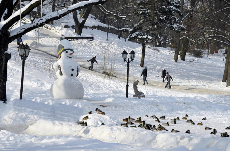 Sneeuwman en het drijven van kinderen in het park stock illustratie
