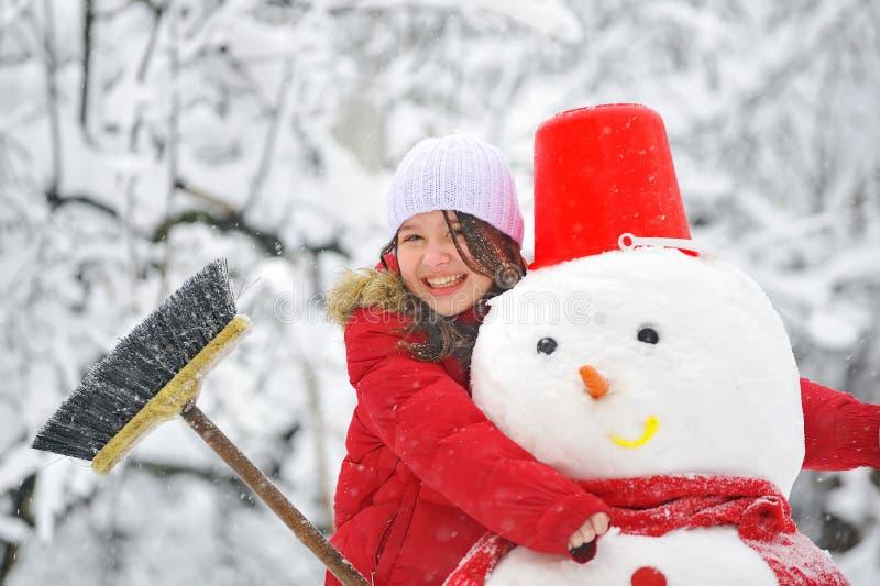 Sneeuwman en jong meisje royalty-vrije stock afbeeldingen