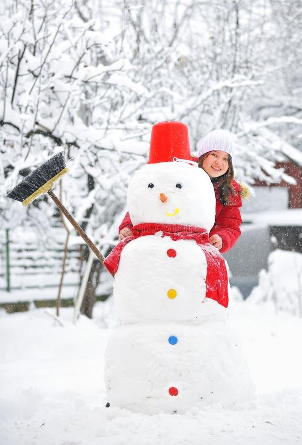 Sneeuwman en jong meisje royalty-vrije stock fotografie