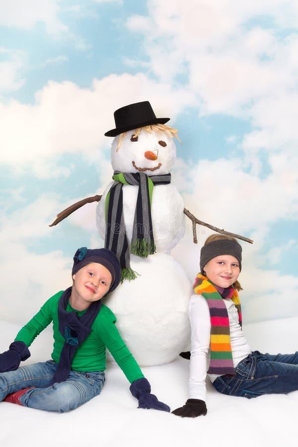 Sneeuwman en meisjes stock foto's