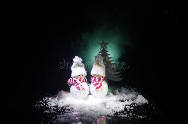 Sneeuwman en Sneeuwvrouw met Hart op sneeuw op donkere achtergrond Nieuwjaar en Kerstmis conceptueel beeld met spar Zoete sneeuwm royalty-vrije stock foto's