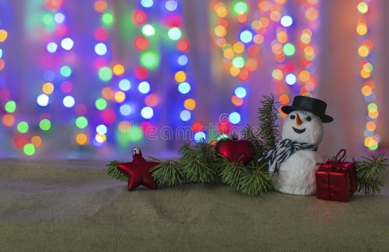 Sneeuwman, Kerstboomtak en Kerstmisspeelgoed op de achtergrond van mooie bokeh van feestelijke lichten met ruimte voor tekst royalty-vrije stock foto's
