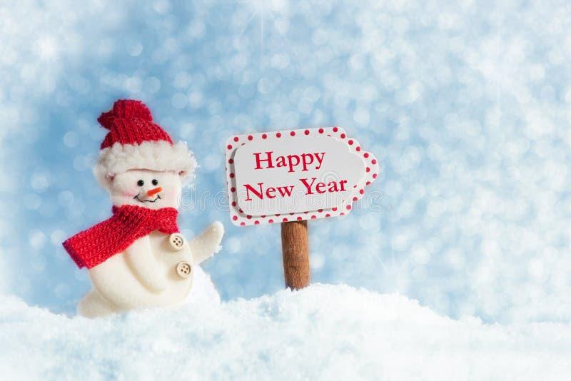 Sneeuwman met Signpost, Gelukkig Nieuwjaar stock fotografie