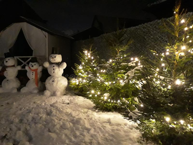 Sneeuwmannen en groene Kerstbomen met slingers royalty-vrije stock foto