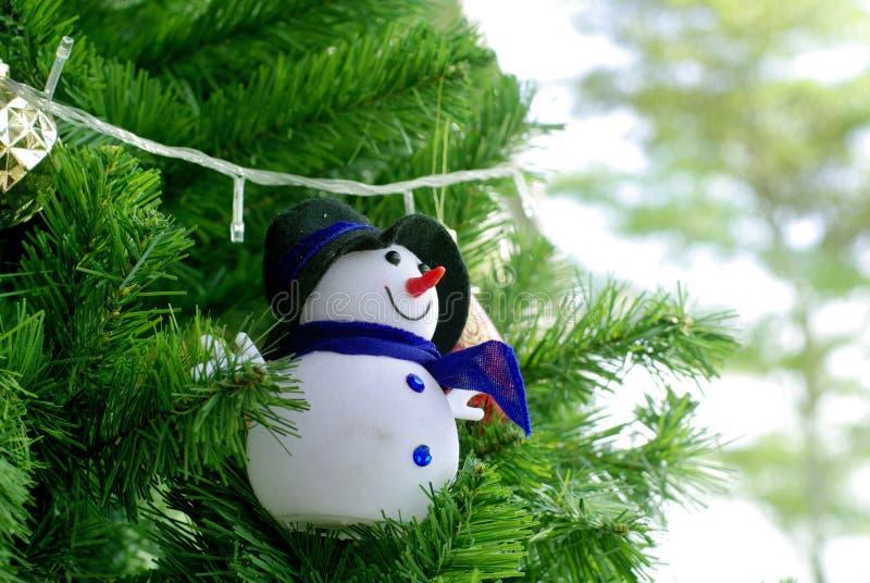Sneeuwmanornament op pijnboomboom stock afbeeldingen
