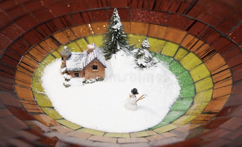 Sneeuwmens met het huis van de sneeuwdekking en Kerstboom in kleurrijke plaat royalty-vrije stock fotografie
