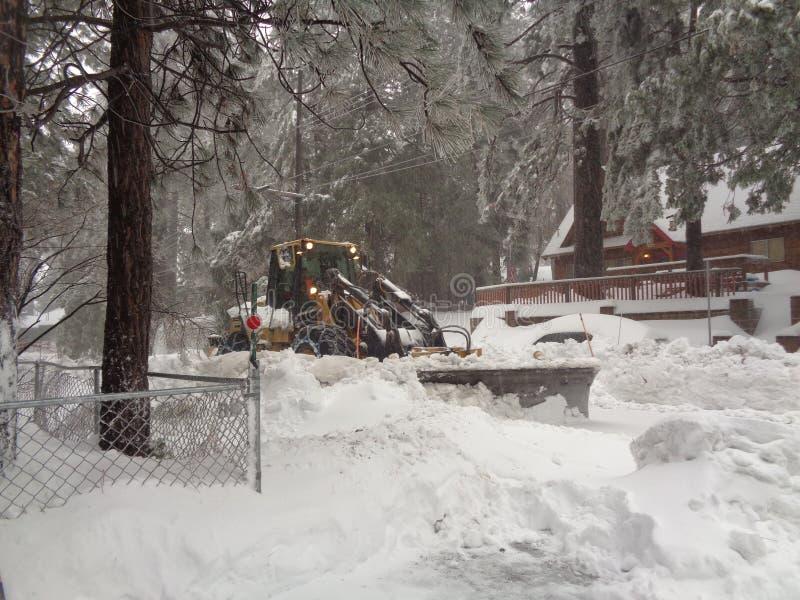 Sneeuwploeg die Woonstraat in het Runnen van de Lentes, San Bernardino Mountains CA ontruimen stock afbeelding