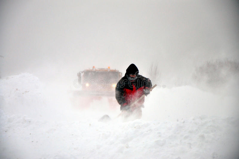 Sneeuwploeg en mens met schop royalty-vrije stock afbeelding