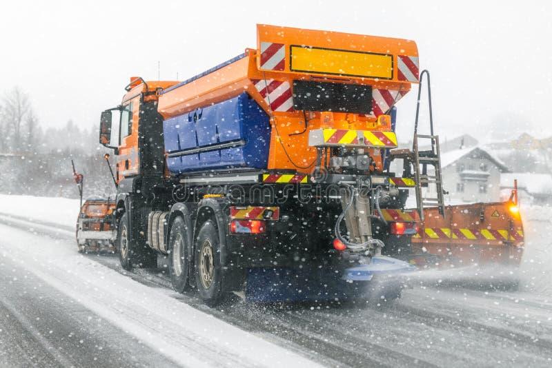 Sneeuwploegvrachtwagen die vuile sneeuw uit stadsstraat of weg verwijderen tijdens zware sneeuwval De situatie van de verkeersweg stock afbeelding