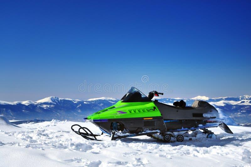 Sneeuwscooter op bergpiek stock foto