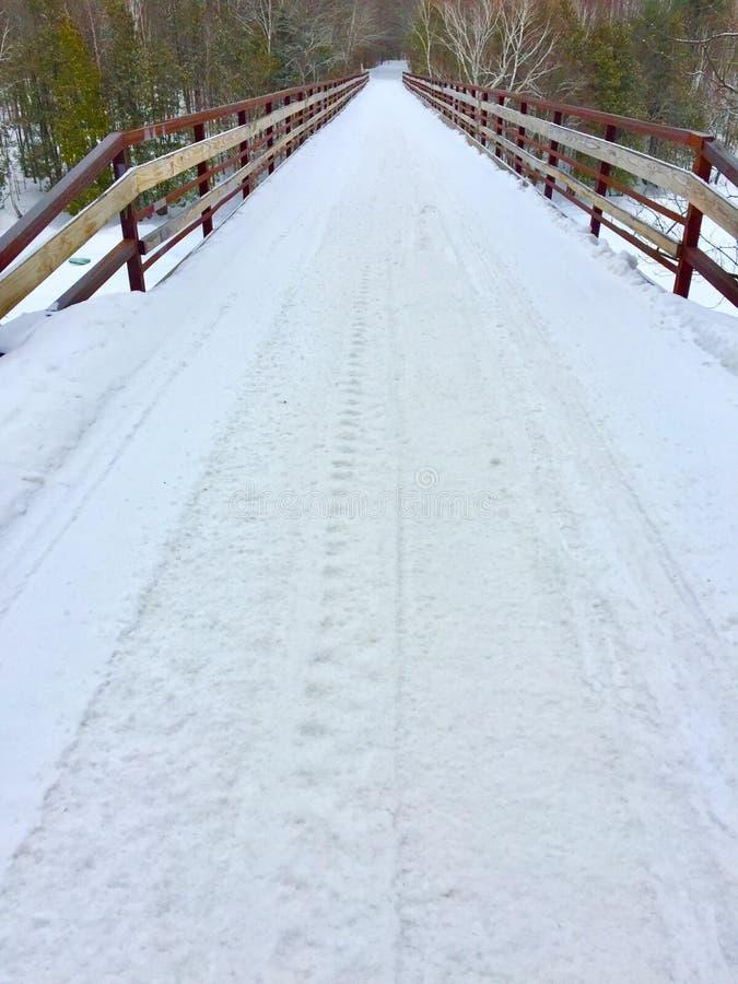 Sneeuwscootersleep op brug over rivier stock afbeeldingen