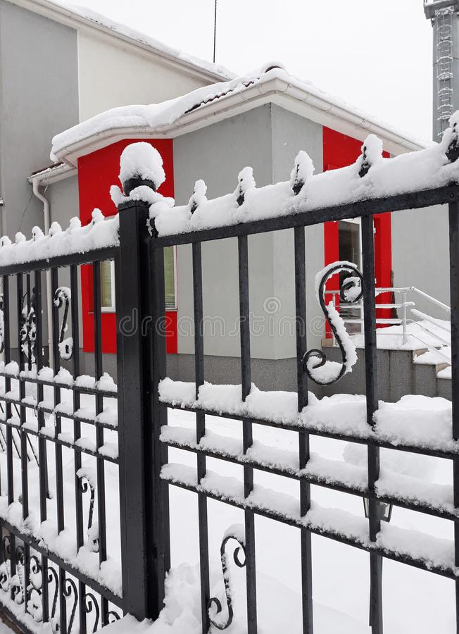 Sneeuwsmeedijzeromheining met rode muren op de achtergrond stock fotografie