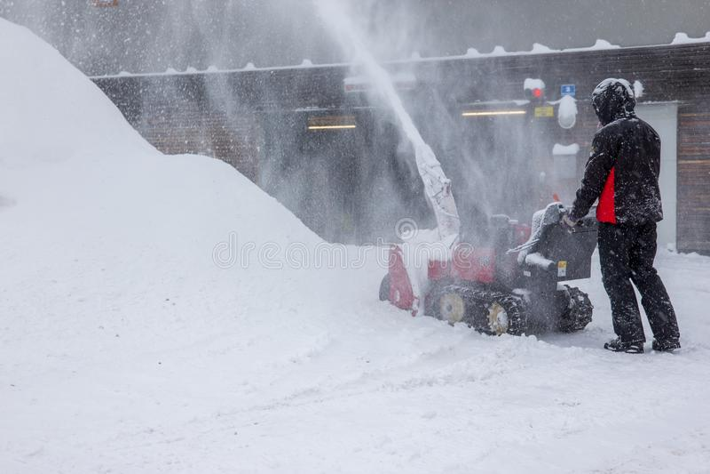 Sneeuwverwijdering met een sneeuwblazer stock afbeeldingen