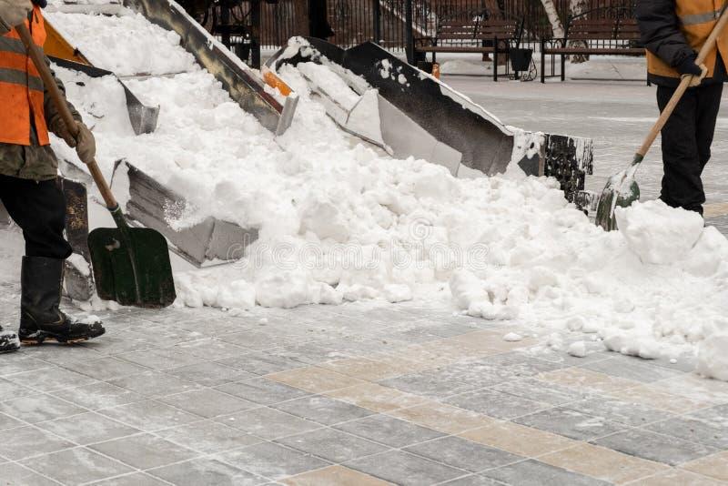 Sneeuwverwijdering op de straten Close-up van een sneeuwploeg en stratemakers met schoppen Mensen en auto's Overvloed van sneeuw  stock fotografie