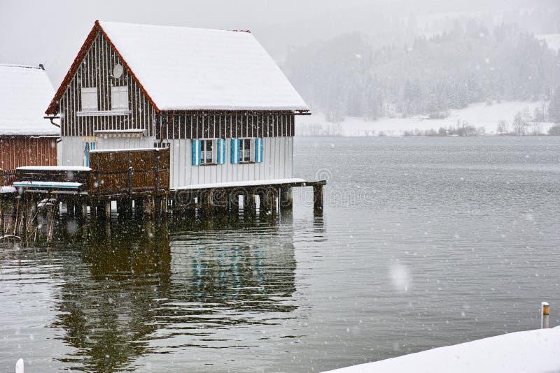 Sneeuwvlaag bij oever van het meerhuis royalty-vrije stock afbeelding