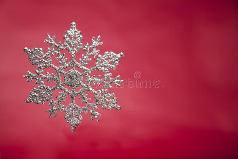 Sneeuwvlok op rode backgroundSnowflake op hout royalty-vrije stock afbeelding
