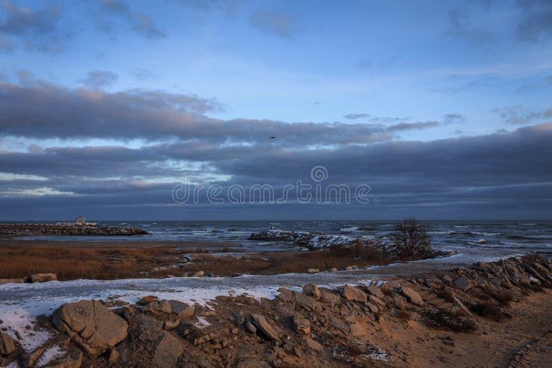 Sneeuwweg aan het overzees tegen een cloudly hemel royalty-vrije stock afbeelding