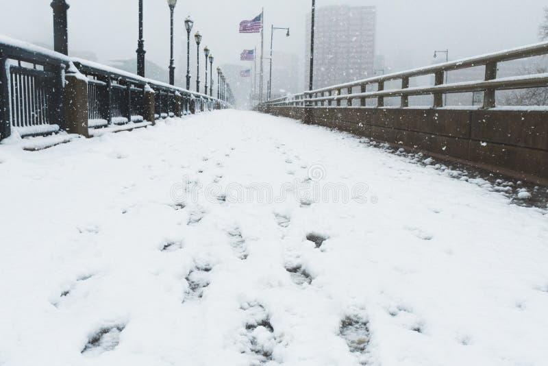 Sneeuwweg die tot stad met Amerikaanse vlaggen leiden die in wind blazen stock afbeeldingen