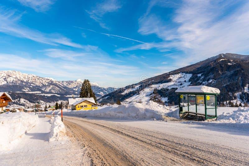Sneeuwweg, sneeuw behandelde bushalte met berg bij de achtergrond Skigebied Schladming, Liezen, Stiermarken, Oostenrijk, Europa royalty-vrije stock foto's