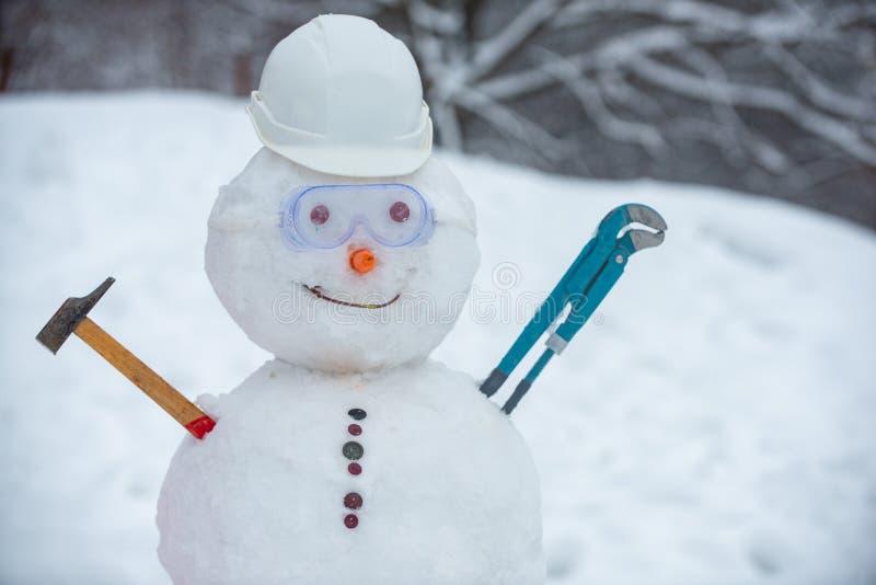 Sneeuwwerker op sneeuwachtergrond Grappig snowman op het werk helm op sneeuwveld Handgemaakte sneeuwpop in de sneeuw buiten royalty-vrije stock afbeelding