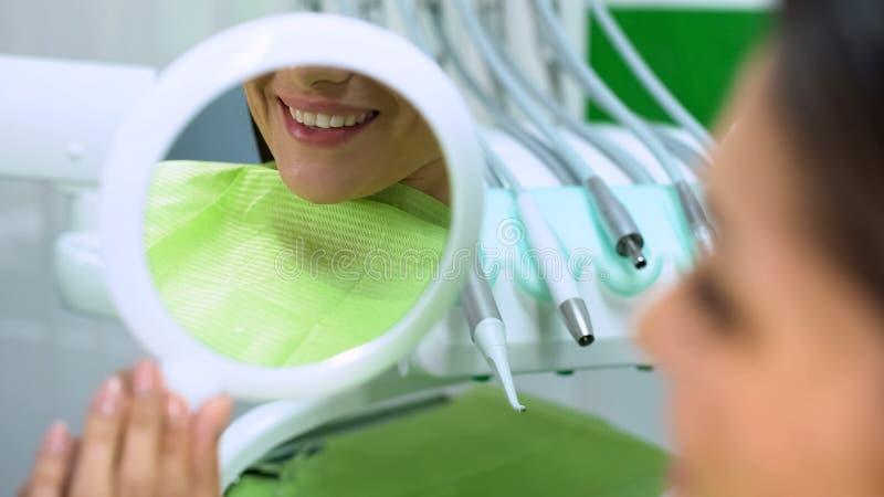 Sneeuwwitte die glimlach in spiegel na de esthetische tandheelkunde van de dichtingsproductplaatsing wordt weerspiegeld royalty-vrije stock afbeeldingen