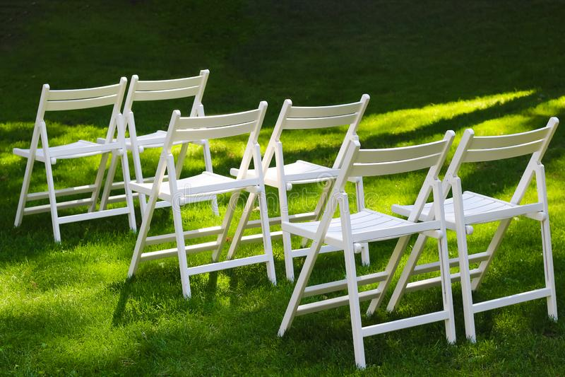 Sneeuwwitte houten stoelen voor gasten bij een openluchthuwelijksceremonie stock fotografie