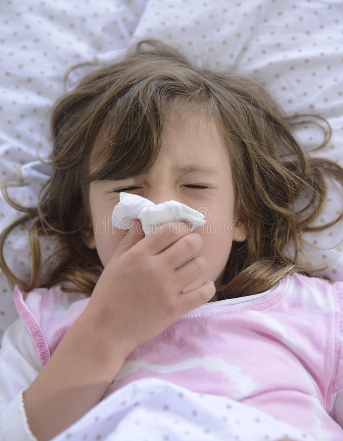 Sneezing child in bed royalty free stock image