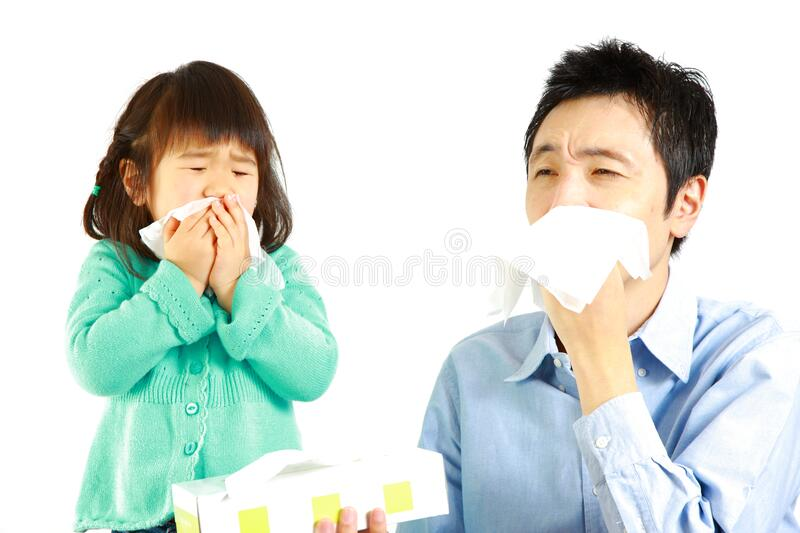 Sneezing father and daughter. Concept shot of Japanese people royalty free stock photo