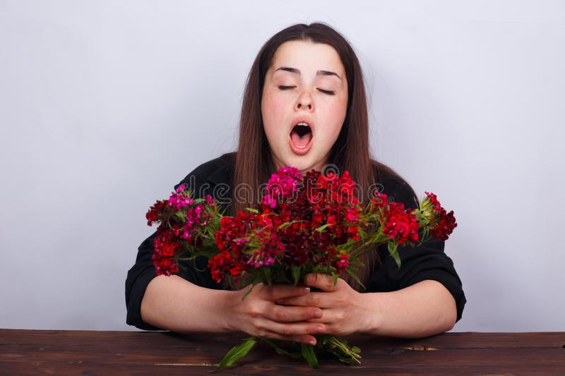 Sneezing young woman holding bouquet of flowers. Allergy, medici stock photos