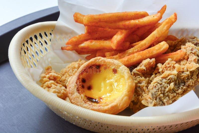 Snel die voedsel in scherpe mand, knapperige gebraden kip, Franse gebraden en ei wordt geplaatst stock foto
