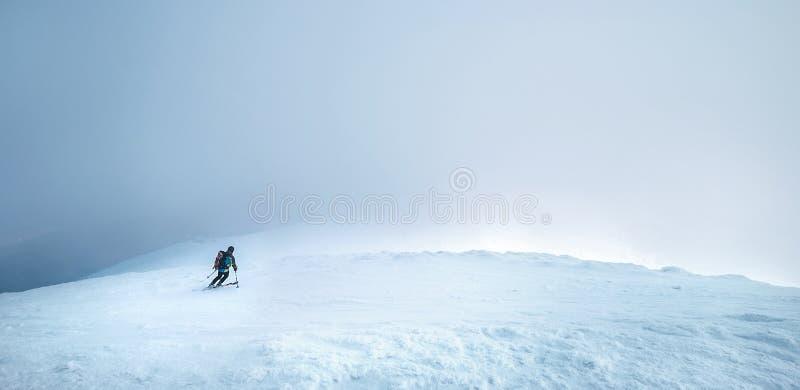 Snel gaande skiërrit onderaan de bergheuvel in de onweerswolken Actief het conceptenbeeld van de de wintersport royalty-vrije stock fotografie