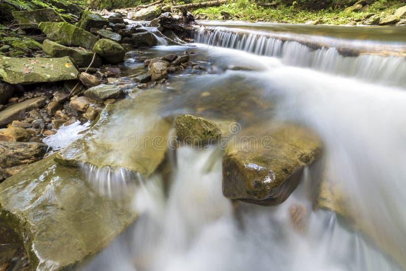 Snel stromende rivierstroom met vlot zijdeachtig water die van grote stenen in mooie watervallen op heldere zonnige de zomerdag v stock afbeeldingen