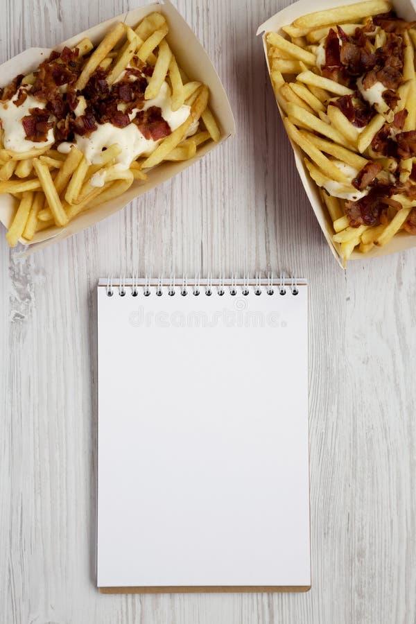 Snel voedsel: frieten met kaassaus en bacon in document vakjes, lege blocnote op een witte houten achtergrond, hoogste mening stock afbeeldingen